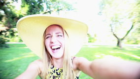 Young woman smiling and taking a selfie. Close up of a beautiful young woman posing, smiling and having fun while taking a selfie in the park stock footage