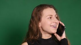 Young woman smiling and talking on her cell phone on a white background. Front view of a young casual woman speaking on. The phone and looks away on green stock video footage