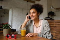 Young woman smiling and talking on mobile phone Royalty Free Stock Images