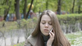 Young woman smiling, talking on mobile phone in park. Hd footage stock video footage