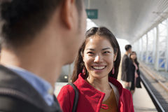 Young woman smiling and talking to man on railway platform, China Stock Image