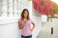 Young woman smiling while texting on smart phone Royalty Free Stock Images