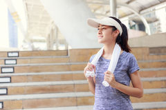 Young  woman smiling  with a towel on her shoulder relaxing after jogging Stock Photo