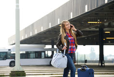 Young woman smiling with travel bags and mobile phone royalty free stock photography