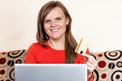 Young woman smiling and  using her credit card for online shoppi Royalty Free Stock Image