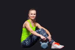 Young woman smiling while using kettlebells Stock Photo