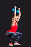 Young woman smiling while using kettlebells Royalty Free Stock Photography