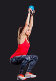 Young woman smiling while using kettlebells Stock Images