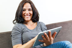 Young woman smiling while using touchpad Royalty Free Stock Photos