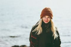 Young Woman smiling walking at winter sea Travel Fashion Lifestyle concept outdoor. Girl wearing orange hat and scarf cold weather Stock Image