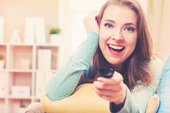 Young woman smiling while watching TV in her house Stock Image