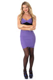 Young Woman Smiling Wearing Tight Purple Short Mini Dress With Arms Folded And High Heels. Sexy Young Woman Smiling Wearing Tight Purple Short Mini Dress Royalty Free Stock Photography