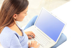 Young woman smiling while working on laptop Royalty Free Stock Photography