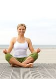 Young woman smiling in yoga pose outdoors royalty free stock photos