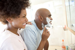 Young woman smiling at young man shaving, side view Royalty Free Stock Photos