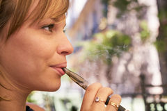 Young Woman Smokes E-Cig Electronic Cigarette Royalty Free Stock Images