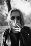 Young woman smokes on the street. Black and white photo Royalty Free Stock Photography