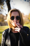 Young woman smokes on the street. Stock Photography