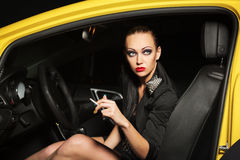 Young woman smoking cigarette in a car Stock Images