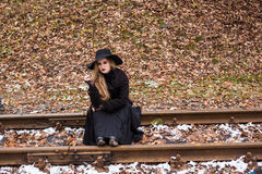 Young woman smoking a cigarette sitting on tracks Royalty Free Stock Images