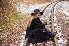 Young woman smoking a cigarette sitting on tracks Royalty Free Stock Photography