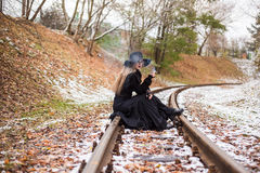 Young woman smoking a cigarette sitting on tracks Stock Photos