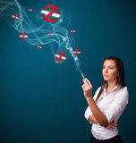 Young woman smoking dangerous cigarette with no smoking signs Stock Images