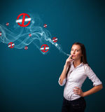 Young woman smoking dangerous cigarette with no smoking signs Stock Image