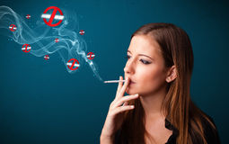 Young woman smoking dangerous cigarette with no smoking signs Royalty Free Stock Images