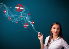 Young woman smoking dangerous cigarette with no smoking signs. Beautiful young woman smoking dangerous cigarette with no smoking signs stock photo
