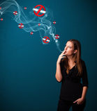Young woman smoking dangerous cigarette with no smoking signs Royalty Free Stock Image