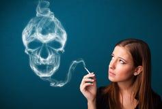 Young woman smoking dangerous cigarette with toxic skull smoke Stock Photography