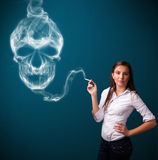 Young woman smoking dangerous cigarette with toxic skull smoke Royalty Free Stock Images