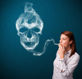 Young woman smoking dangerous cigarette with toxic skull smoke Stock Image