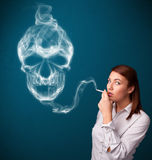 Young woman smoking dangerous cigarette with toxic skull smoke Stock Photo