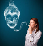 Young woman smoking dangerous cigarette with toxic skull smoke Stock Photos