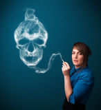 Young woman smoking dangerous cigarette with toxic skull smoke Royalty Free Stock Image