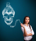 Young woman smoking dangerous cigarette with toxic skull smoke Royalty Free Stock Photos