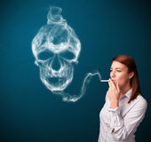 Young woman smoking dangerous cigarette with toxic skull smoke Royalty Free Stock Photography
