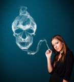 Young woman smoking dangerous cigarette with toxic skull smoke. Pretty young woman smoking dangerous cigarette with toxic skull smoke Royalty Free Stock Photos