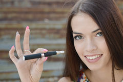 Young woman smoking electronic cigarette (e-cigarette) Royalty Free Stock Photo