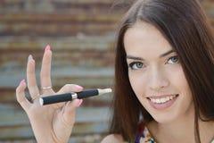 Young woman smoking electronic cigarette (e-cigarette) Royalty Free Stock Photo