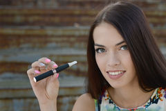 Young woman smoking electronic cigarette (e-cigarette) Stock Photography