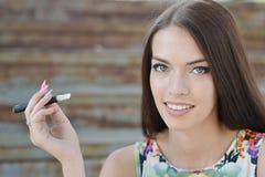 Young woman smoking electronic cigarette (e-cigarette) Stock Image