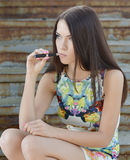 Young woman smoking electronic cigarette (e-cigarette) Royalty Free Stock Photography