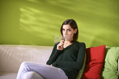 Young woman smoking electronic cigarette at home Stock Photos