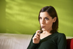 Young woman smoking electronic cigarette at home Royalty Free Stock Photo