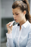 Young woman smoking electronic cigarette outdoor office building Stock Photos