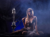 A young woman smoking a hookah Stock Image