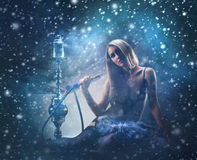 A young woman smoking a hookah on the snow Royalty Free Stock Photo